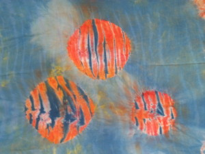 This piece started as orange hand-dyed rayon.  I then wrapped it on a pole (arashi shibori), discharged and over-dyed it.  Then I masked off the circles and dyed it again.  This has possibilities, too, don't you think?